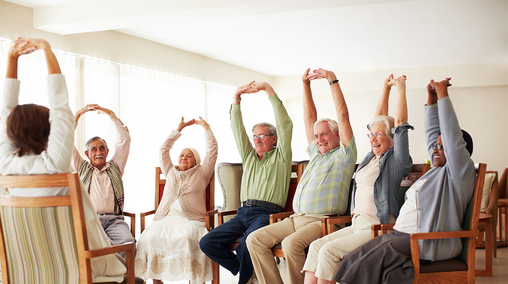 A cadence chandler worker leading a group of elderly people in a group stretch