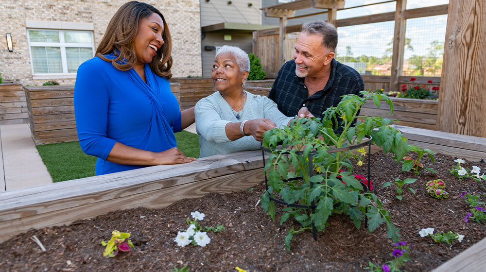 Senior living residents stop to admire flower garden during a tour with staff member