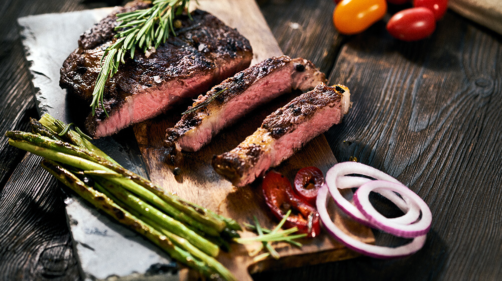 plate of sliced steak on a wooden carving board