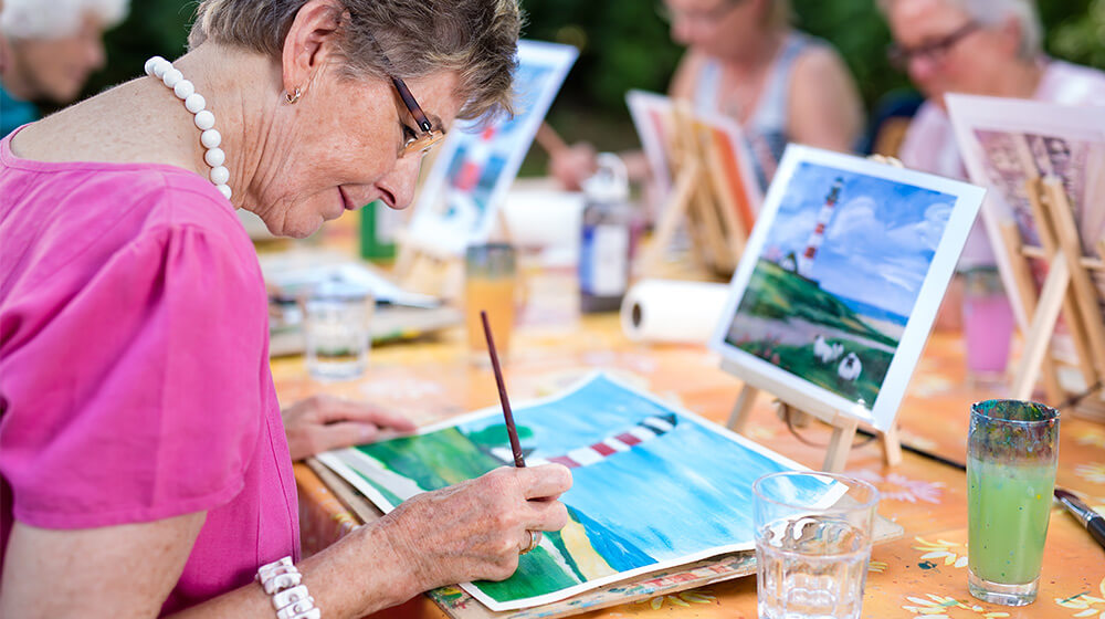 Older adults paint at outdoor table in group class
