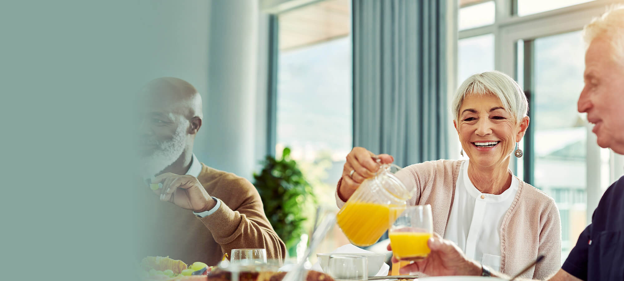 Group of friends gather at breakfast smiling in brightly lit room