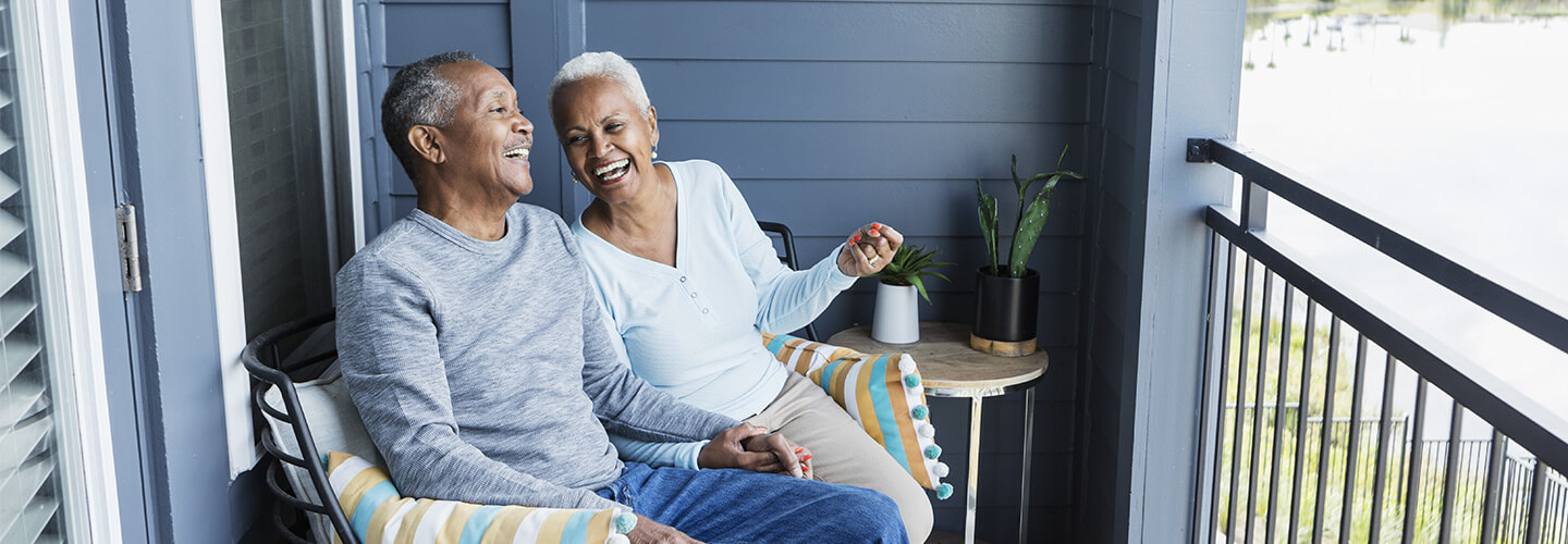 Couple laughs on elevated porch near lake
