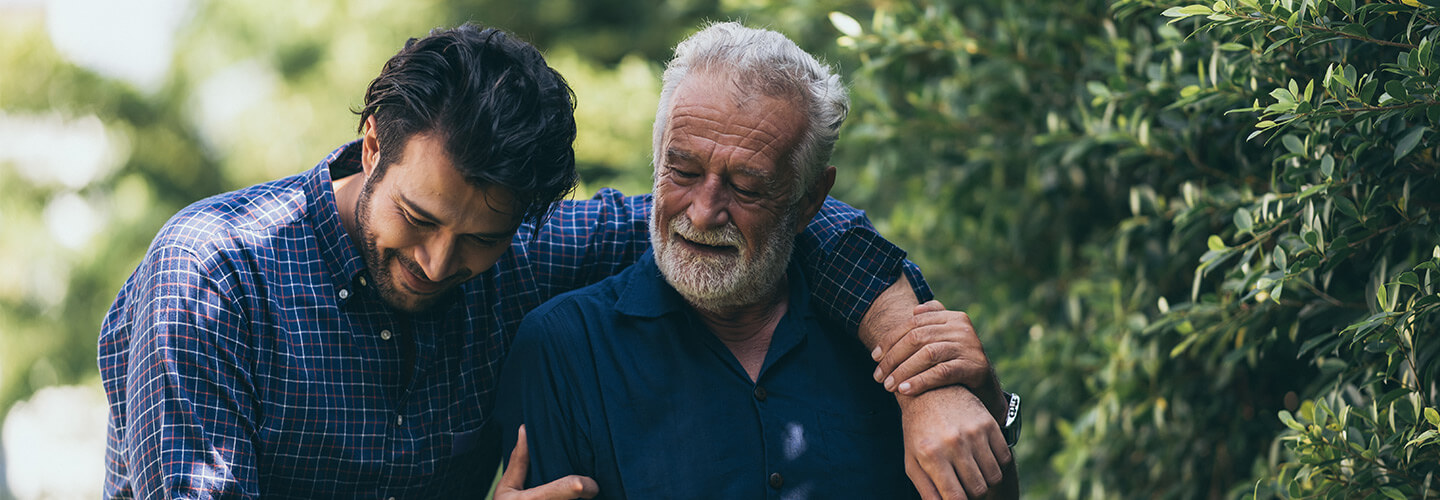 Older man takes a walk with younger man in a sunny, scenic grove
