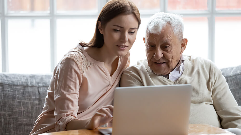 Nurse takes a look at computer with older gentleman