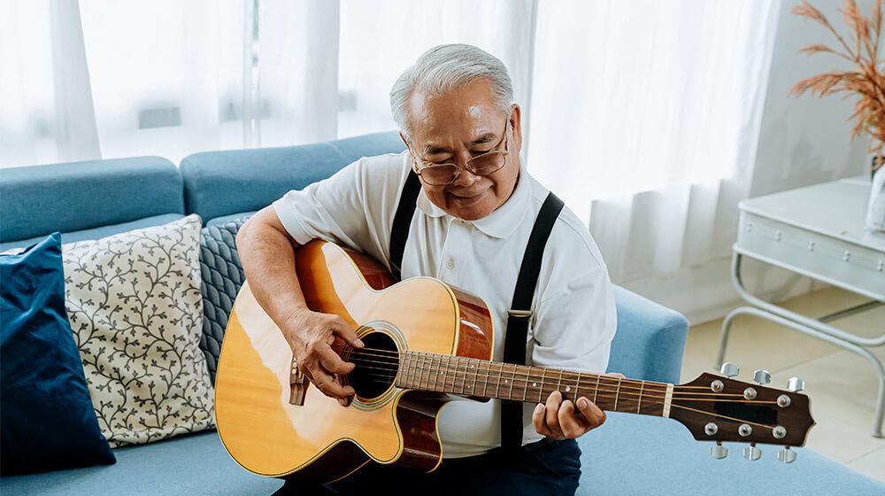 Older gentleman practices guitar attentively