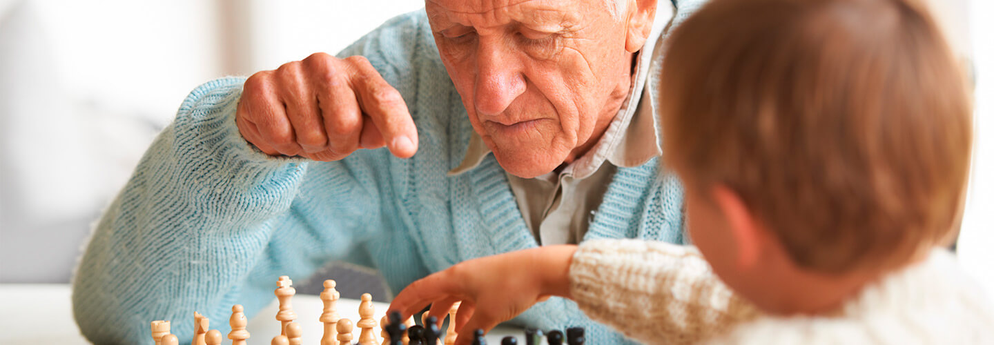 Older gentleman explains chess move to young boy