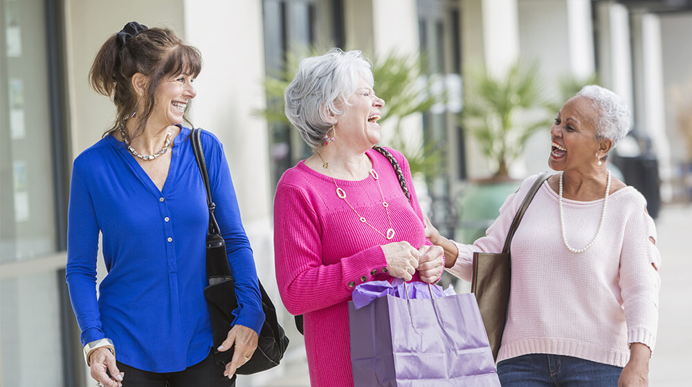 Older friends go shopping in outdoor pavilion and laugh while holding their purchases