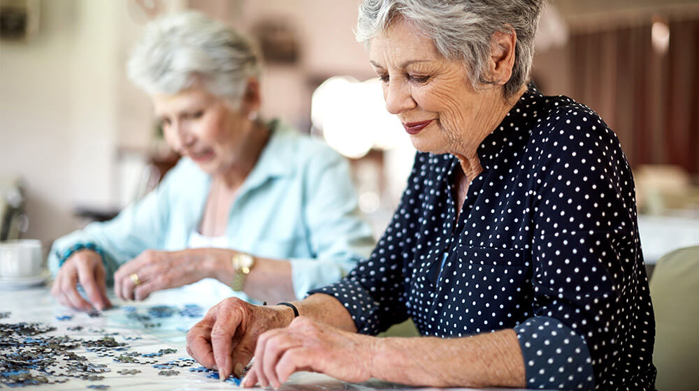 Elderly woman in polka dot button up doing a puzzle with another elderly woman