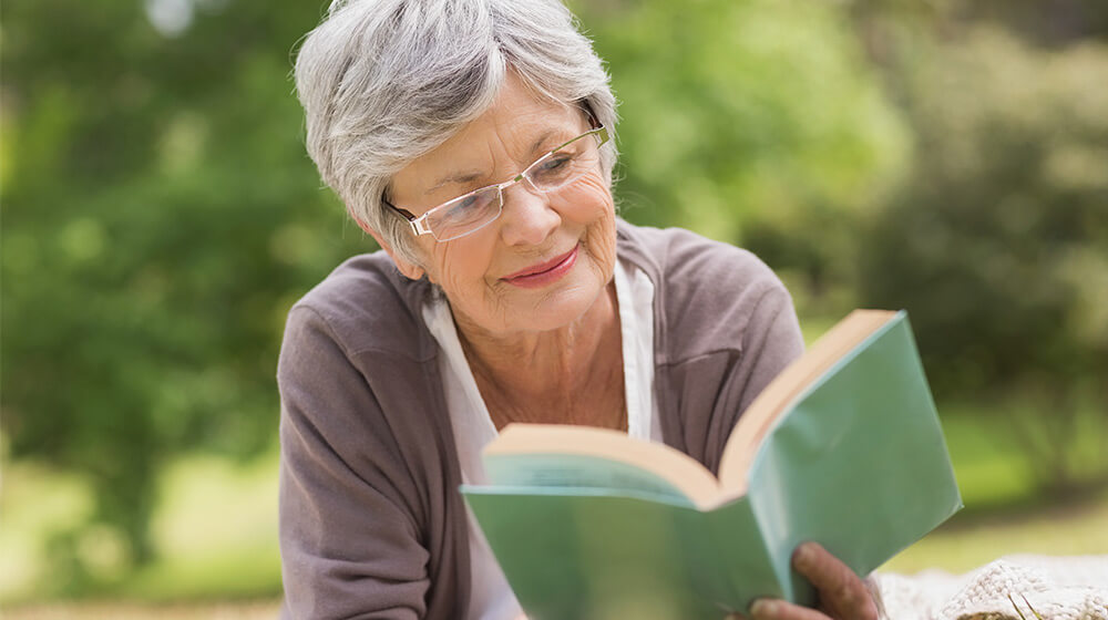 Mature women and friend share the experience of reading outdoors